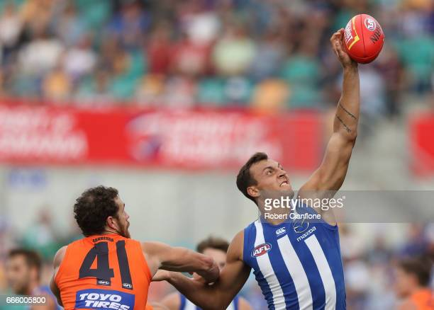 Braydon Preuss of the Kangaroos gets to the ball ahead of Shane Mumford of the Giants during the round three AFL match between the North Melbourne...