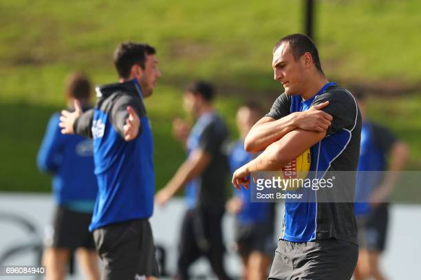 Braydon Preuss of the Kangaroos holds the ball as Todd Goldstein looks on during a North Melbourne Kangaroos AFL training session at Arden Street...
