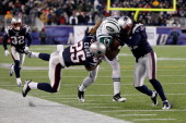 Braylon Edwards of the New York Jets is hit as he runs for yards after the catch by Patrick Chung and Brandon Meriweather of the New England Patriots...