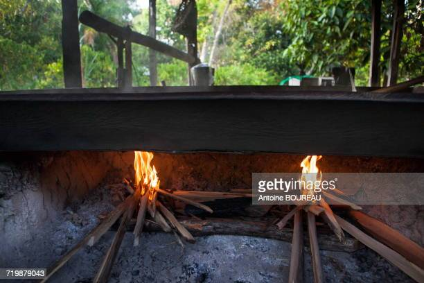 Brazil, Amapa, Fire above Masseira, oven made up with 4 wooden sides and an iron plate, the men have for mission to dry and cook the manioc flour by making it slide on the iron plate to aerate it at the most, Ribeirinhos people living in Amazonia along th