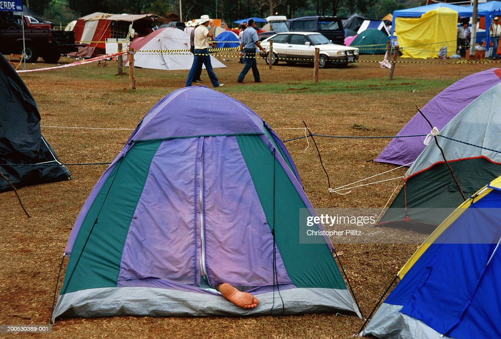 Brazil, Barretos Rodeo, person sticking foot out of tent in campsite : Stock Photo
