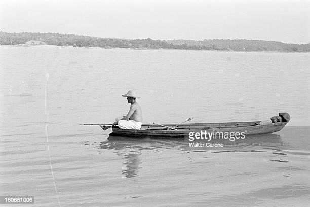 Brazil Brésil Période 19501955 Reportage sur le Brésil un chasseur de Caïman noir assis à la proue de sa pirogue observe le fleuve Amazone ou un de...