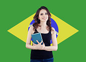Brazil concept with cute woman student against the Brazilian flag background. Travel in Brazil and learn portuguese language