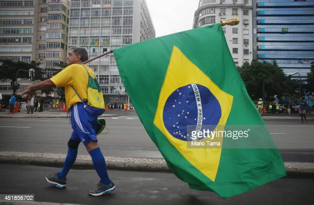 Brazil fan carries his national flag on Copacabana Beach ahead of the 2014 FIFA World Cup semifinal match between Brazil and Germany on July 8 2014...