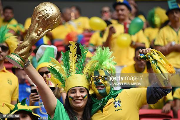 Brazil fans hold a replica of the World Cup trophy as they cheer prior to the Group A football match between Cameroon and Brazil at the Mane...
