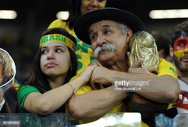 Brazil fans look dejected following the 2014 FIFA World Cup Brazil Semi Final match between Brazil and Germany at Estadio Mineirao on July 08 2014 in...