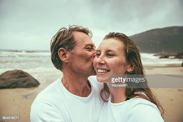 Brazil, Florianopolis, man kissing woman on the beach at a rainy day