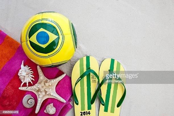 Brazil football, flip flops and shells on sand