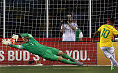 Brazil forward Neymar scores on a direct penalty kick as the United States goalkeeper Tim Howard guessed right but can't make the save during the...
