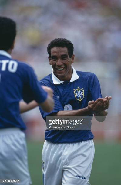 Brazil midfielder Zinho pictured celebrating with a 'cradle the baby' hand gesture as he runs to congratulate goalscorer Bebeto during play in the...