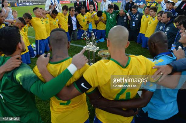 Brazil players and coaches get together and seem to pray as they celebrate their victory with the trophy during the Final of the Toulon Tournament...