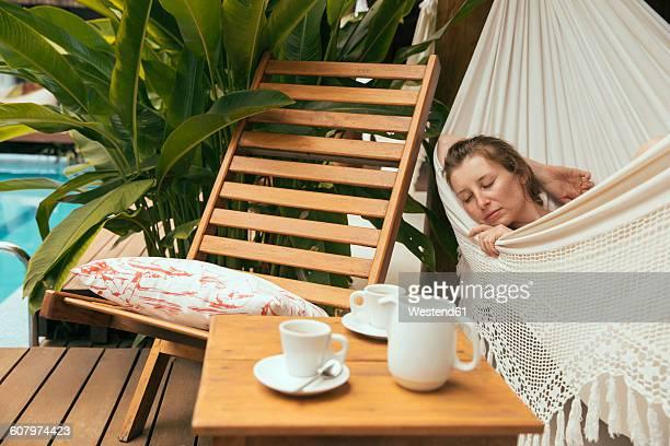Brazil, Porto Seguro, portrait of woman sleeping in a hammock