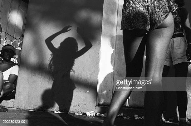 Brazil, Porto Seguro, woman dancing casting shadow on wall (B&W)
