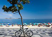 Brazil, Rio de Janeiro, bicycle against tree with tourists on Panema Beach in background