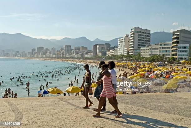 Brazil Rio de Janeiro Crowds at Ipanema beach with yellow umbrellas blue sea and sky swimmers in sea and hotels along the Avenue Vieira Souto with...