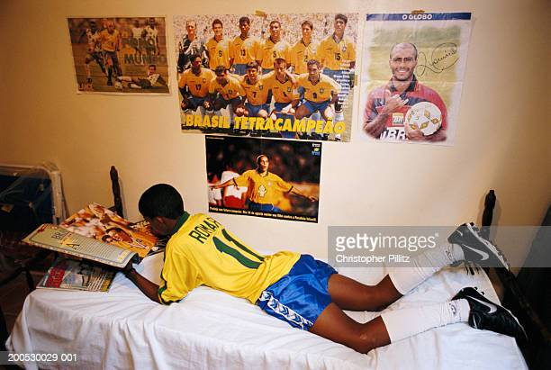 Brazil, Rio de Janerio, boy lying on bed looking at football album