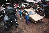 Brazil, Sao Paolo City, men playing football in car scrapyard