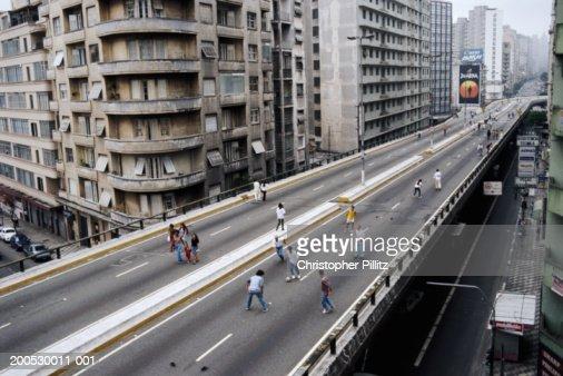 Brazil, Sao Paolo, people playing football on city highway : Stock Photo