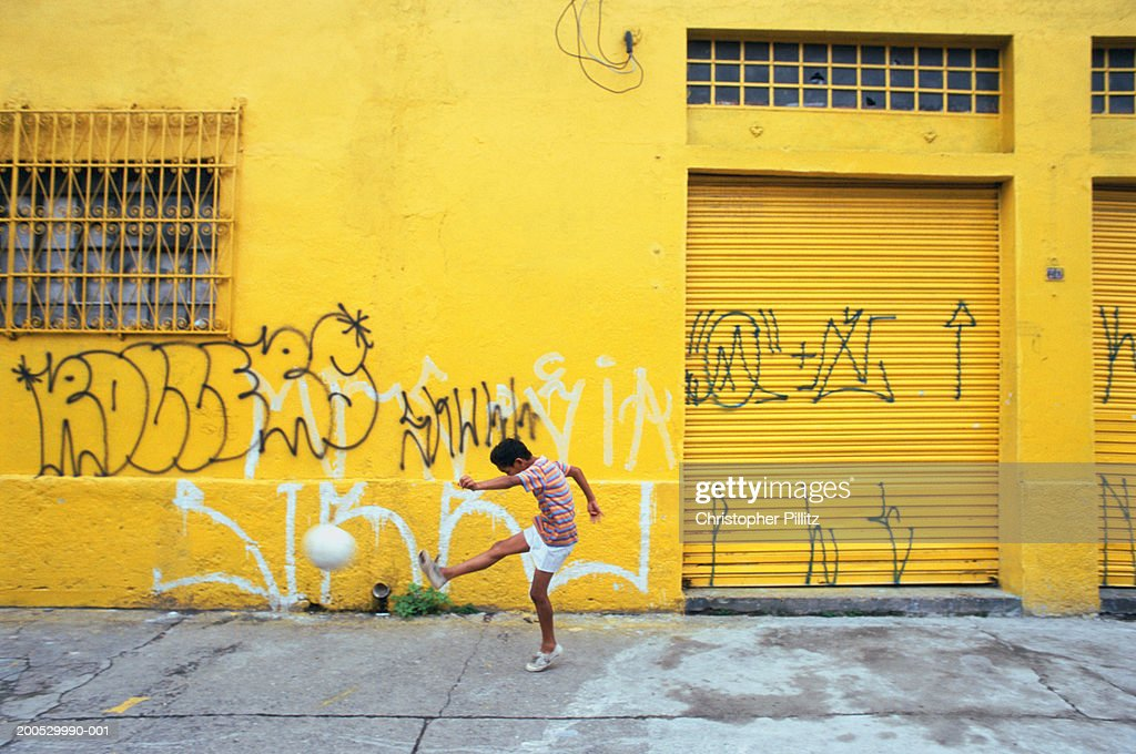 Brazil, Sao Paulo City, boy kicking football in street