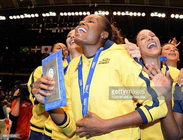 Brazil team captain Fabiana Claudino holding her trophy of Most Valuable Player celebrates their gold medal victory with teammates during the awards...