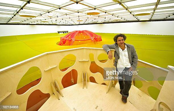 Brazilan artist Ernesto Neto poses for photographers on a platform above his installation entitled 'Horizonmembranenave' at the Hayward Gallery in...