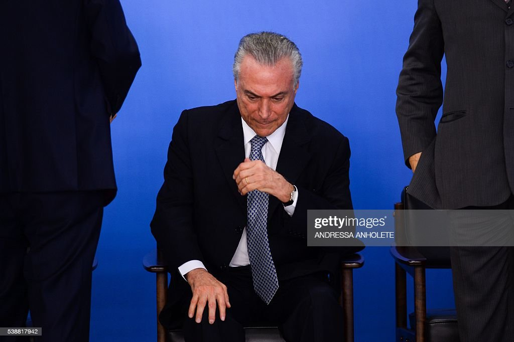 TOPSHOT Brazilian acting President Michel Temer attends a meeting with business leaders next to his Finance Minister Henrique Meirelles at Planalto...