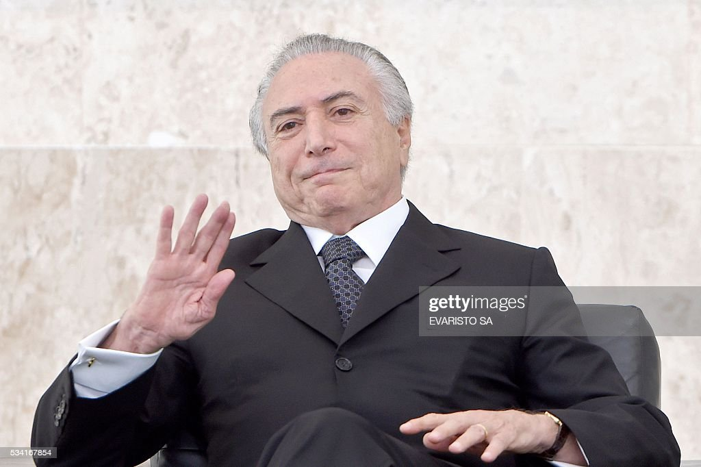 Brazilian acting President Michel Temer waves during a ceremony of the presentation of credentials of Ambassadors at Planalto Palace in Brasilia on May 25, 2016. / AFP / EVARISTO SA