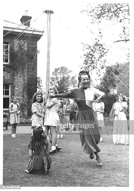 Brazilian actress singer and dancer Carmen Miranda dances round a maypole in Weston Turville England 1948 | Location Weston Turville England UK