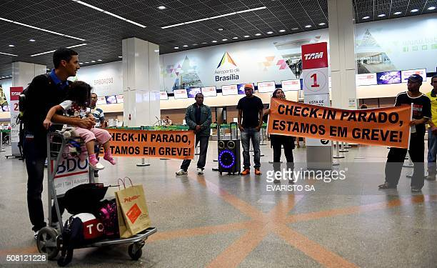Brazilian airline workers display a banner during a strike at Brasilia Airport on February 3 2016 Brazilian airline workers held a strike over a pay...
