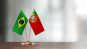 Brazilian and Portuguese flag pair on desk over defocused background. Horizontal composition with copy space and selective focus.