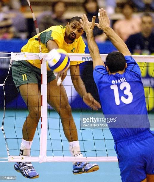 Brazilian Anderson Rodrigues spikes the ball through Italian defender Andrea Giani during the World Cup men's volleyball tournament at the Hamamatsu...