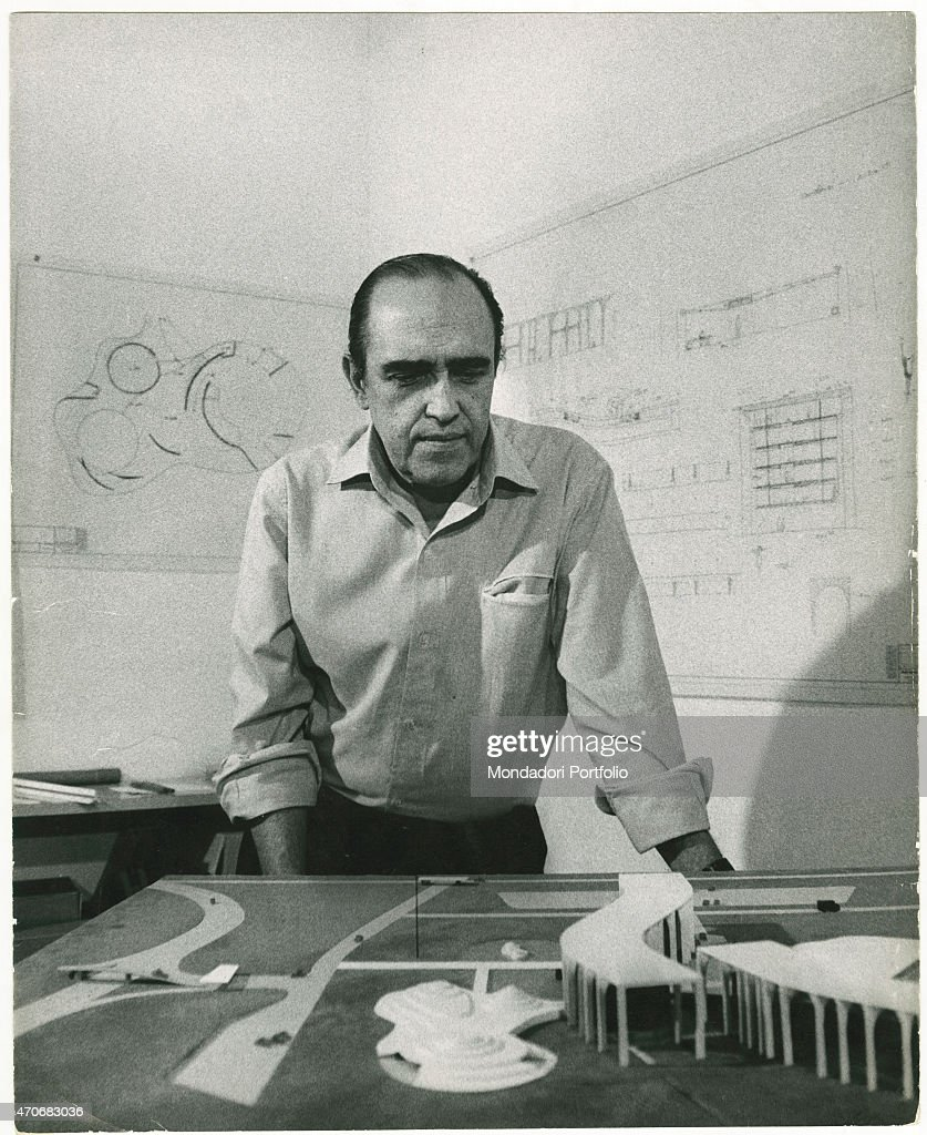'Brazilian architect <a gi-track='captionPersonalityLinkClicked' href=/galleries/search?phrase=Oscar+Niemeyer&family=editorial&specificpeople=161539 ng-click='$event.stopPropagation()'>Oscar Niemeyer</a> observing the scale model of Palazzo Mondadori in his office. Behind him, the drawings of some projects hanging. Milan, 1968 (Photo by Walter Mori\Mondadori Portfolio via Getty Images)'