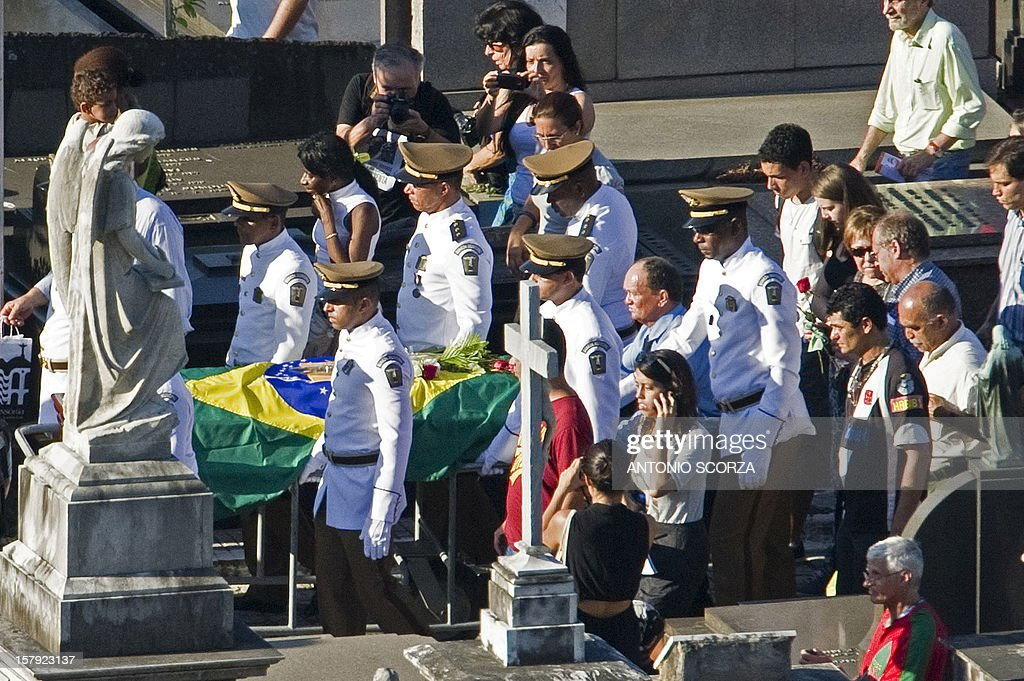 Brazilian architect Oscar Niemeyer's coffin is carried at Sao Joao Batista cementery in Rio de Janeiro, Brazil on December 7, 2012. Niemeyer, the Brazilian icon who revolutionized modern architecture and designed much of the country's futuristic capital Brasilia, died at 104. AFP PHOTO/ANTONIO SCORZA