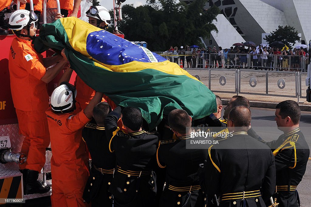 Brazilian architect Oscar Niemeyer's funeral coffin arrives at Planalto Palace in Brasilia, Brazil, on December 06, 2012. Niemeyer, the Brazilian icon who revolutionized modern architecture and designed much of the country's futuristic capital Brasilia, died in Rio de Janeiro Wednesday at 104. The body will return to Rio de Janeiro for another funeral wake followed by the burial, according to Rio de Janeiro's Mayor Eduardo Paes. AFP PHOTO / Evaristo SA