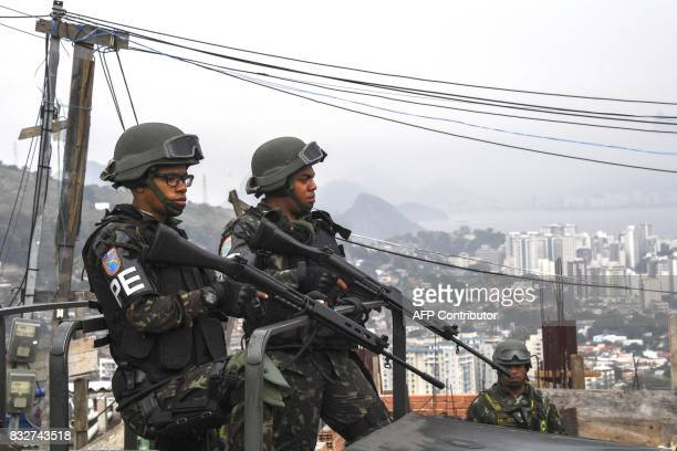 Brazilian Army Military Police personnel stand guard on high spot during a predawn antigang operation in Niteroi greater Rio de Janeiro Brazil on...