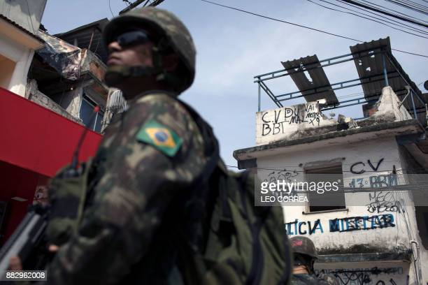 A Brazilian army soldier stands guard in front of a destroyed police post during a security operation at Barbante favela in Rio de Janeiro Brazil on...