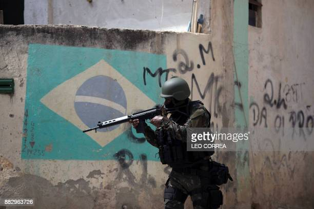 A Brazilian army soldier takes position in an alley during a security operation at Barbante favela where earlier in the week alleged drug traffickers...