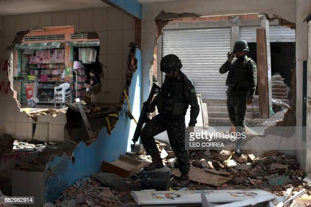 TOPSHOT Brazilian army soldiers check damages at a destroyed police post during a security operation at Barbante favela in Rio de Janeiro Brazil on...