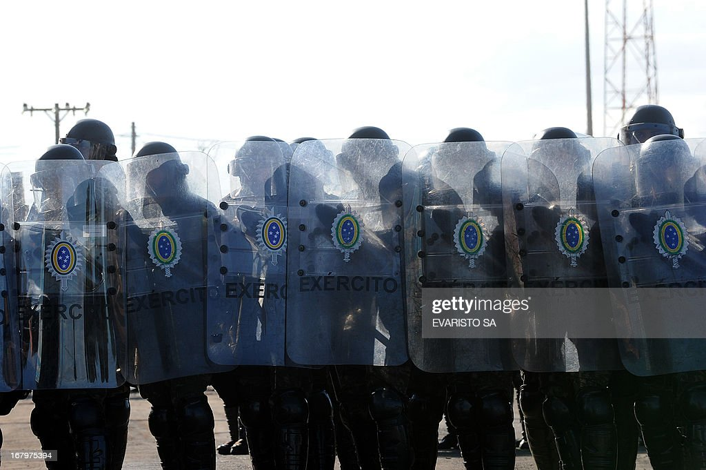 Brazilian Army soldiers in riot gear conduct a drill at the Fire Department headquarters in Brasilia, on May 3, 2013, as part of the security measures ahead of the Confederation Cup which will be held next June for the 2014 FIFA World Cup and the 2016 Olympics Games. AFP PHOTO / Evaristo SA