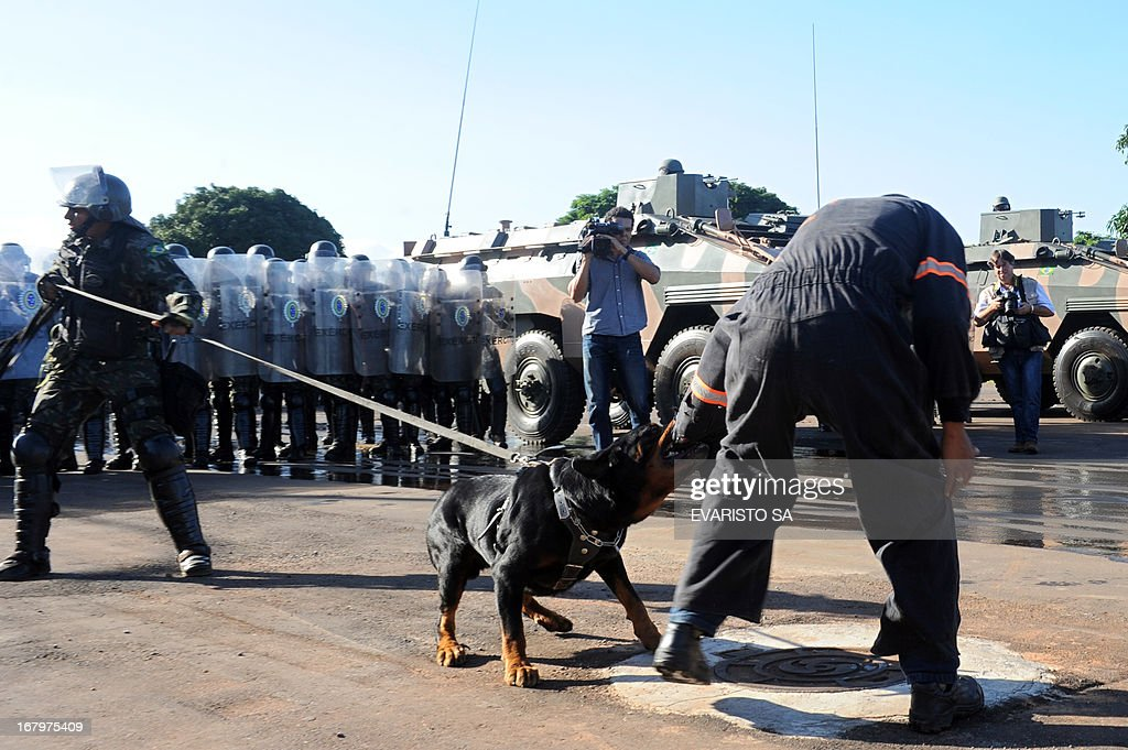 Brazilian Army soldiers in riot gear, supported by armoured personnel carriers and trained dogs conduct a drill at the Fire Department headquarters in Brasilia, on May 3, 2013, as part of the security measures ahead of the Confederation Cup which will be held next June for the 2014 FIFA World Cup and the 2016 Olympics Games. AFP PHOTO / Evaristo SA