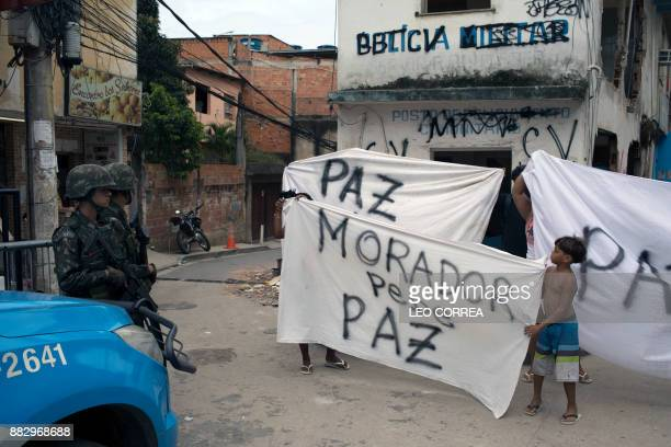 Brazilian army soldiers stand guard as locals display a banner reading 'Residents ask for peace' in front of a destroyed police post during a...