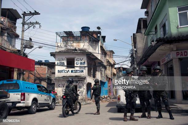 Brazilian army soldiers stand guard in front of a destroyed police post during a security operation at Barbante favela in Rio de Janeiro Brazil on...