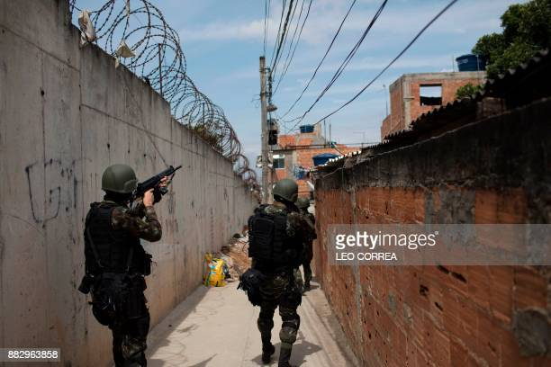 Brazilian army soldiers take position in an alley during a security operation at Barbante favela where earlier in the week alleged drug traffickers...
