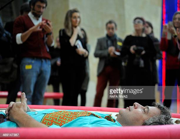 Brazilian artist Ernesto Neto lies on his artwork 'Looking at the Sky' as he looks at his installation 'The Falling Body' during the presentation of...