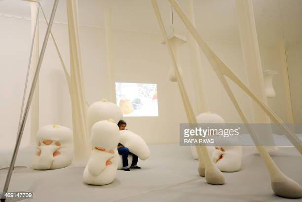 Brazilian artist Ernesto Neto sits in one of his 'Humanoids' during the presentation of his exhibition 'The Body That Carries Me' on February 13 2014...