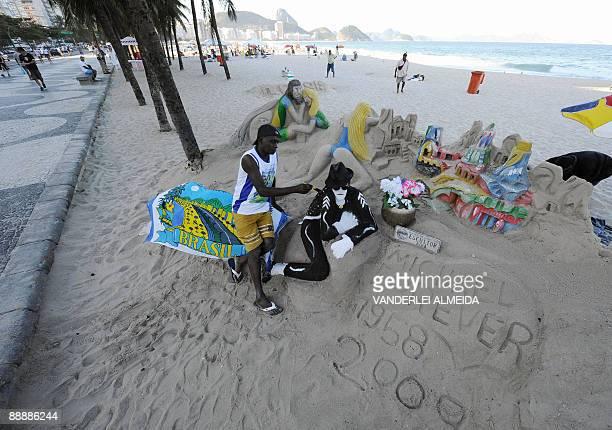 Brazilian artist Ubiratan da Conceicao dos Santos gives the final touches to the sand sculpture of Michael Jackson he created at Copacabana Beach in...