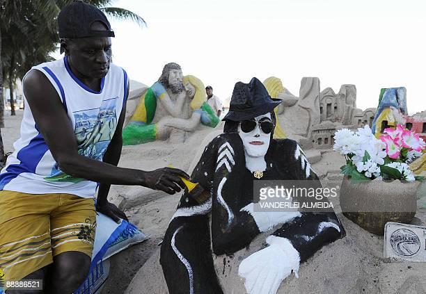 Brazilian artist Ubiratan da Conceicao dos Santos gives the finishing touches to his sand sculpture of Michael Jackson in Rio de Janeiro's Copacabana...