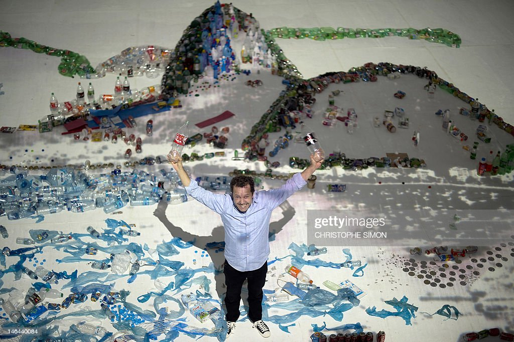 Brazilian artist Vik Muniz poses in the middle of his piece made of trash, portraying the sugar loaf in Rio de Janeiro, on June 16, 2012. The UN conference, which marks the 20th anniversary of the Earth Summit -- a landmark 1992 gathering that opened the debate on the future of the planet and its resources -- is the largest ever organized, with some 50,000 delegates. AFP PHOTO / Christophe Simon