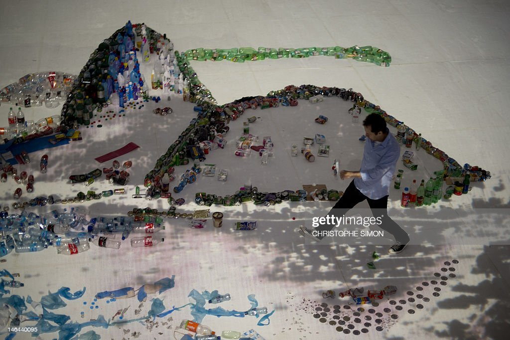 Brazilian artist Vik Muniz walks over his piece made of trash, portraying the sugar loaf in Rio de Janeiro, on June 16, 2012. The UN conference, which marks the 20th anniversary of the Earth Summit -- a landmark 1992 gathering that opened the debate on the future of the planet and its resources -- is the largest ever organized, with some 50,000 delegates. AFP PHOTO / Christophe Simon