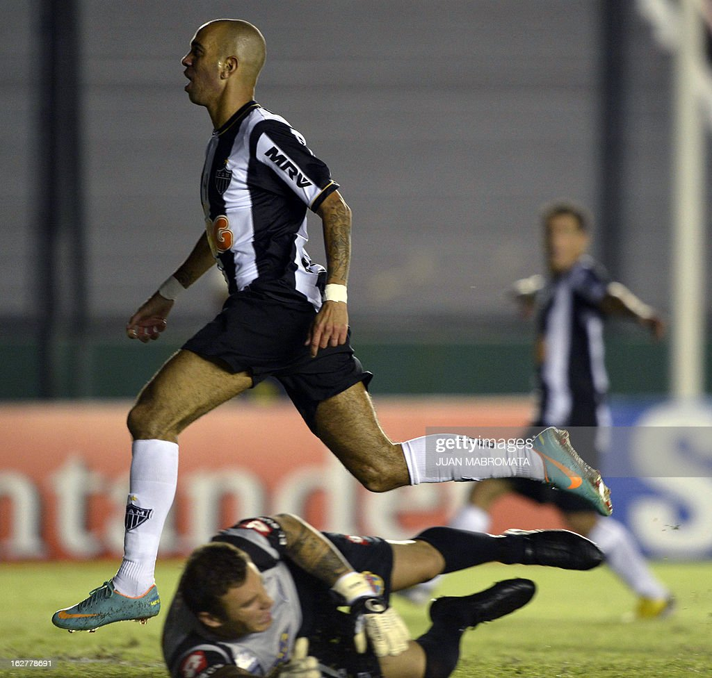 Brazilian Atletico Mineiro's forward Diego Tardelli (top) celebrates after scoring a goal against Argentina's Arsenal FC during their Copa Libertadores 2013 group 3 football match at Arsenal stadium in Sarandi, Buenos Aires, Argentina, on February 26, 2013. AFP PHOTO / Juan Mabromata
